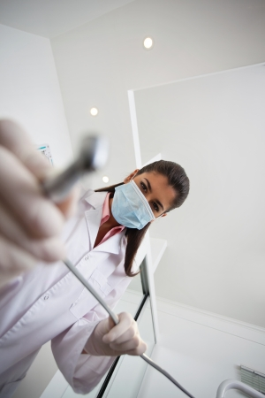 dentist drill: Low angle view of female dentist holding drill