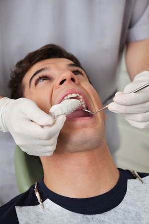 Dentist putting in molds in patients mouth photo