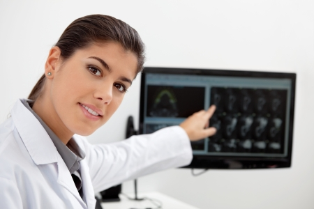 Portrait of pretty female dentist showing teeth x-ray on screen photo