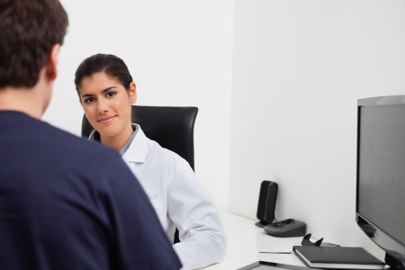 Female dentist sitting at her desk in front of patient at clinic photo