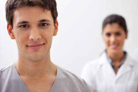 male dentist: Portrait of male doctor standing with female doctor standing in background Stock Photo