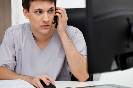 Doctor working on computer while talking on cell phone photo