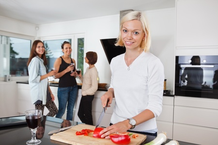 Portrait of happy female cutting vegetables while friends having drink in background