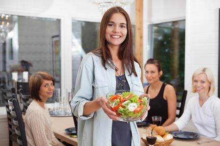 Portrait of happy female holding bowl of vegetables while her friends sitting in background photo