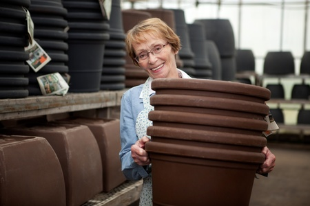 Portrait of a senior worker in garden center with large plant pots photo