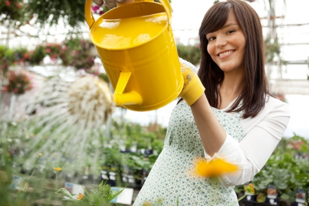 Portrait of an attractive female water plants with a watering can photo