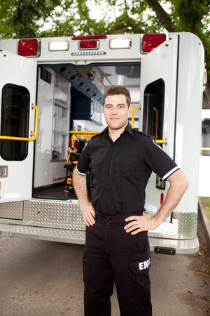 Male paramedic standing in front of ambulance in residential area photo