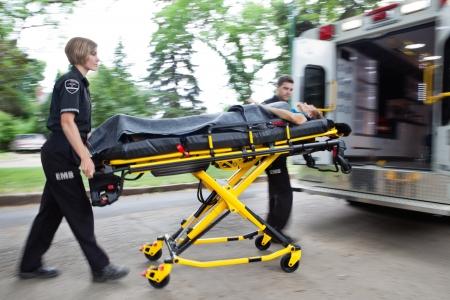 paciente en camilla: Hombre y mujer equipo de la ambulancia por tierra una mujer mayor en el veh�culo Foto de archivo