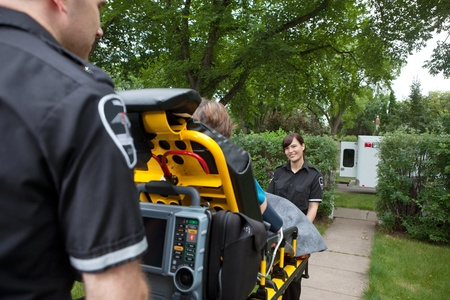 Two ambulance workers pushing elderly patient to vehicle Stock Photo - 11048172