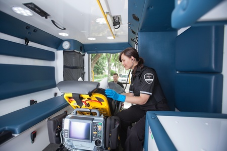 EMT worker listening to heart rate of patient photo