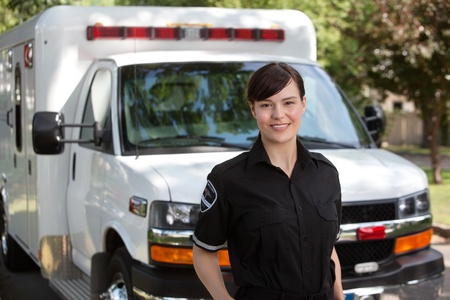 cfr: Portrait of attractive paramedic standing in front of ambulance