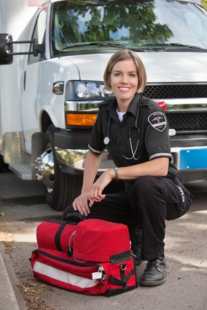 Portrait of a happy paramedic kneeling by a portable oxygen unit and ambulance photo