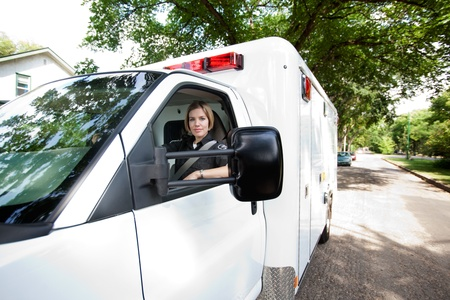Portrait of a paramedic woman driving an ambulance in a residential city area photo