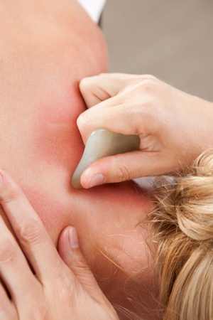 stimulate: Female receiving gua sha treatment to neck and shoulders