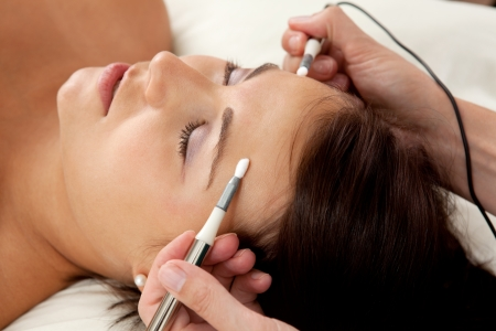 魅力的な女性患者の顔に電気鍼美容・ アンチエイジング治療の一環として