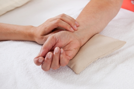 acupuntura china: El pulso se toma en la muñeca de una mujer de mediana edad de