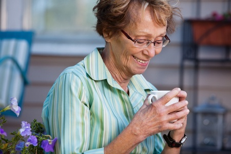 pensioner: Senior woman enjoying a warm drink in back yard