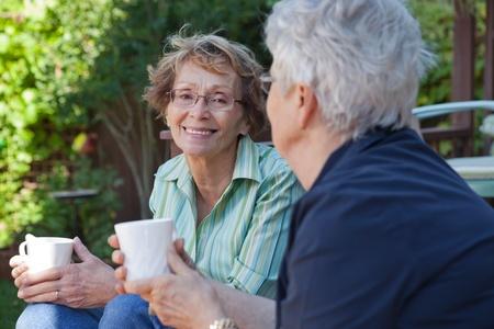 mujeres mayores: Dos mujeres mayores que disfrutan de un refresco al aire libre calientes