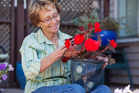 Cheerful senior woman looking at flower pot photo