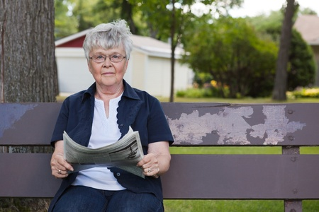 Portrait of senior woman holding newspaper, sitting on park bench Stock Photo - 11048125