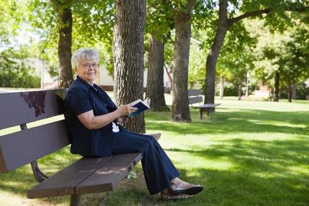 banc de parc: Portrait de femme �g�e assise sur un banc de parc en lisant un livre