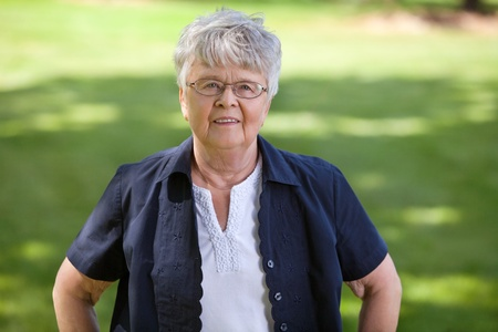 Portrait of senior woman standing in park photo