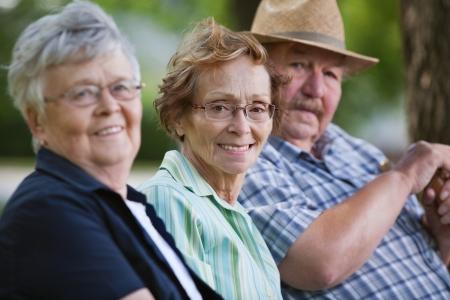 Portrait of senior friends sitting together in park photo