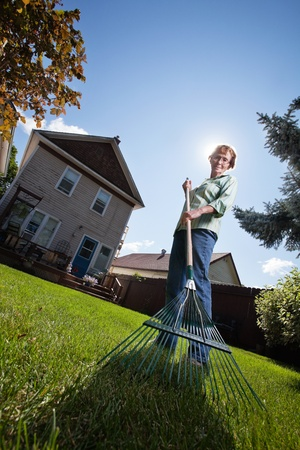 yard work: Low angle view of senior woman holding rake