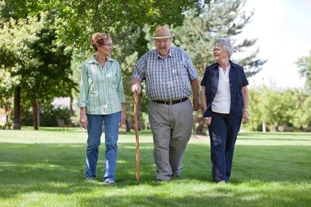 senior citizen: Three senior friends walking in park during summer Stock Photo