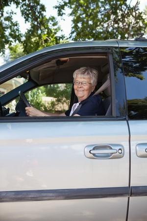 Portrait of pretty senior woman driving car photo