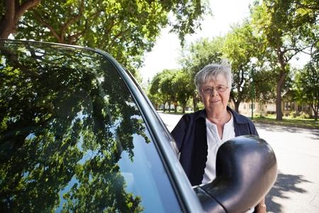 Portrait of a senior woman standing near car photo