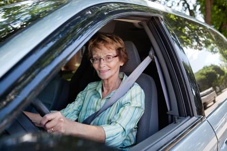 senior citizen: Portrait of senior woman smiling while driving car