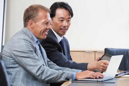 Two multi-ethnic colleagues working together on a computer photo
