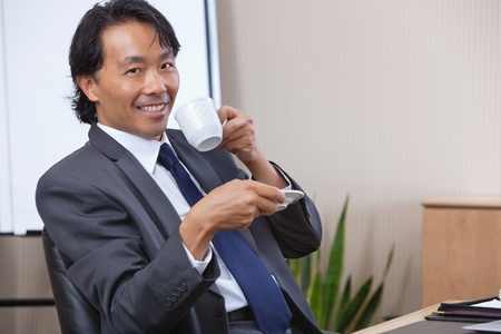 Portrait of smiling businessman having coffee photo