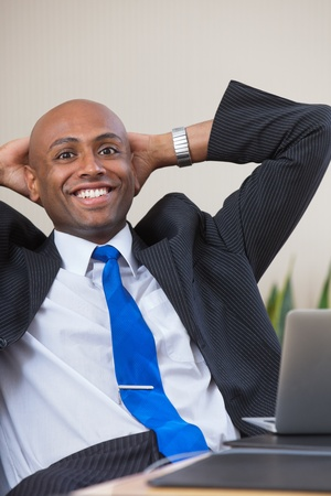 relaxed business man: Executive leaning back in chair with hands on back of head