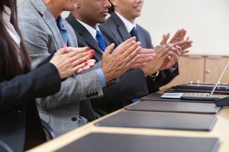 manos aplaudiendo: Hombres de negocios sentado en una fila y aplaudiendo