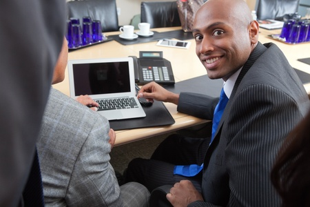 african businessman: Portrait of an African American businessman working with colleague in office Stock Photo