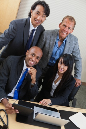 Portrait of happy business people working on laptop together Stock Photo - 11048481