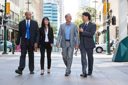 caucasian ethnicity: Group of happy business people walking together on street
