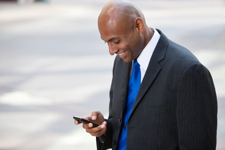 Portrait of an African American businessman text messaging photo