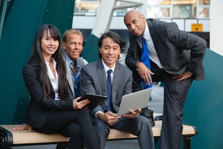asian business team: Portrait of smiling business people using electronic gadgets