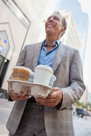 Smiling businessman holding takeaway coffee cups photo