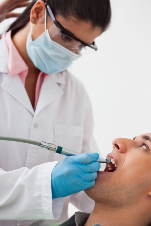 mouth cavity: Female dentist working on patients teeth at clinic Stock Photo