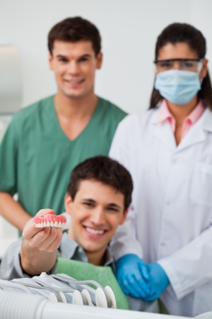 periodontics: Male patient showing dental molds with dentist standing in background with her colleague Stock Photo