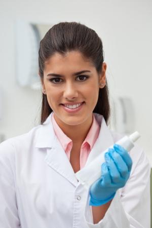Portrait of female dentist holding toothpaste photo