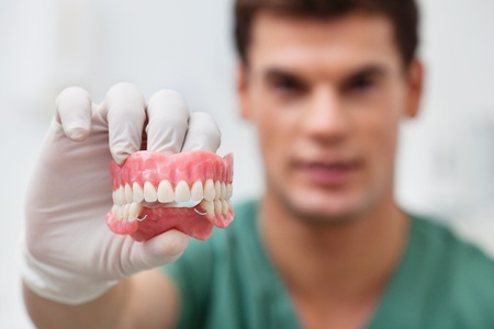 Close-up of male practitioner holding dental mold photo