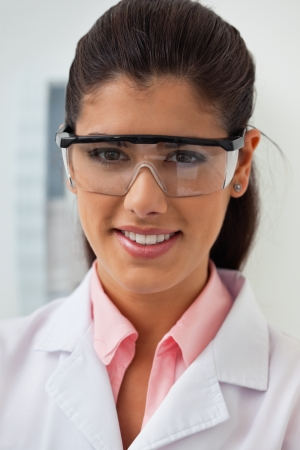 protective eyewear: Portrait of smiling female dentist at her clinic Stock Photo