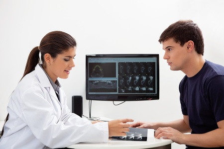 Female dentist discussing report with patient at clinic photo