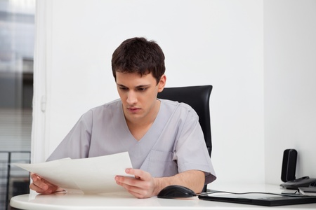 Serious male doctor reading reports of patient Stock Photo - 11173326