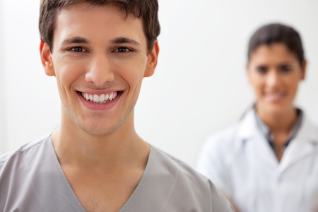 Portrait of happy male doctor standing with female doctor standing in background Stock Photo - 11173397